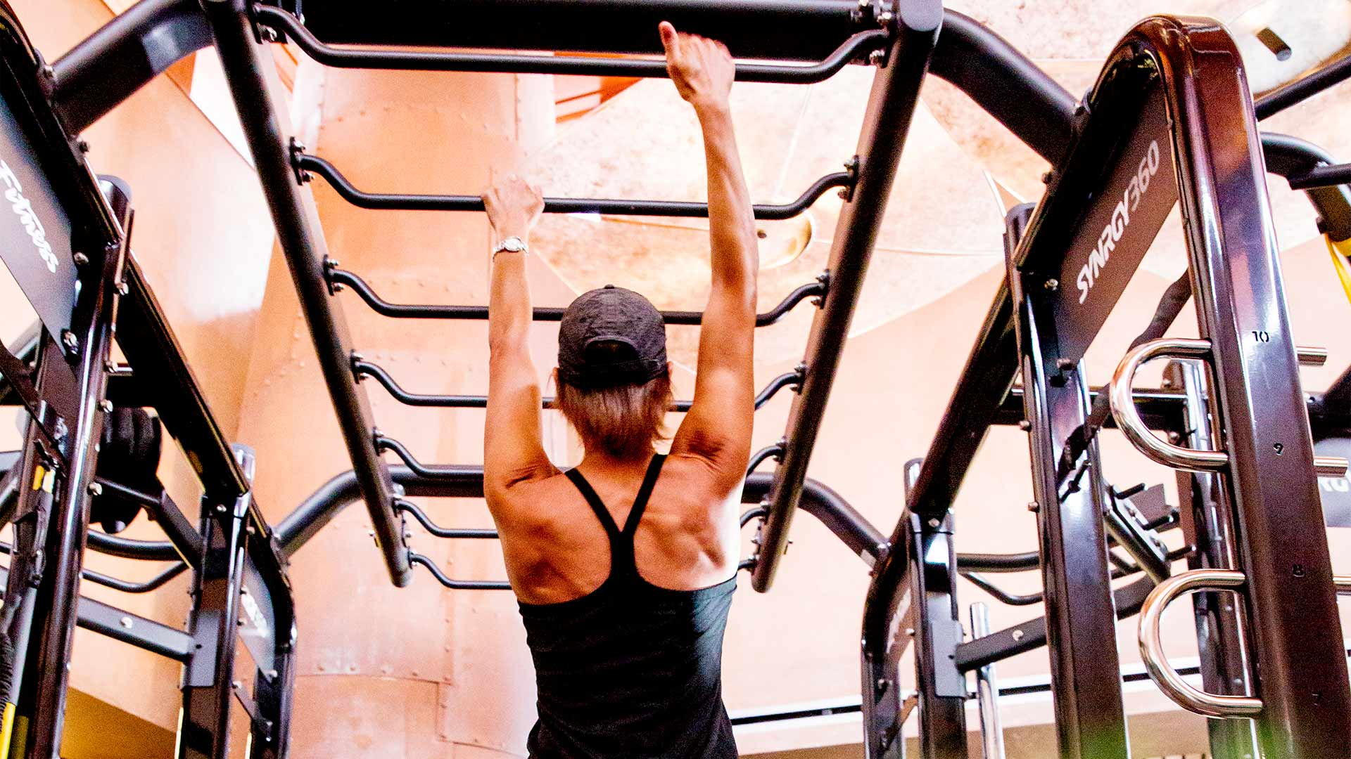 a woman in a black workout tank top and hat is working her way across rungs like monkey bars