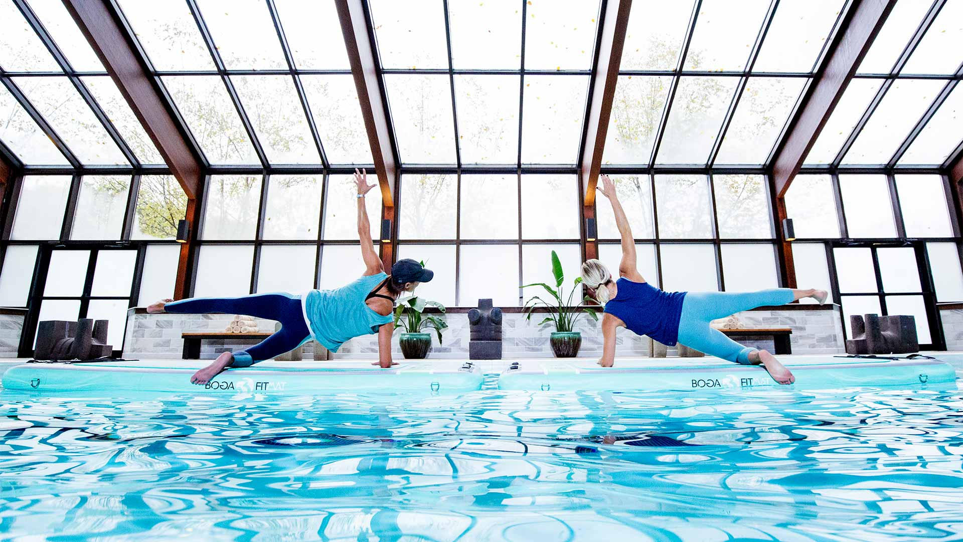 two people is blue workout gear are doing side planks at the edge of a pool