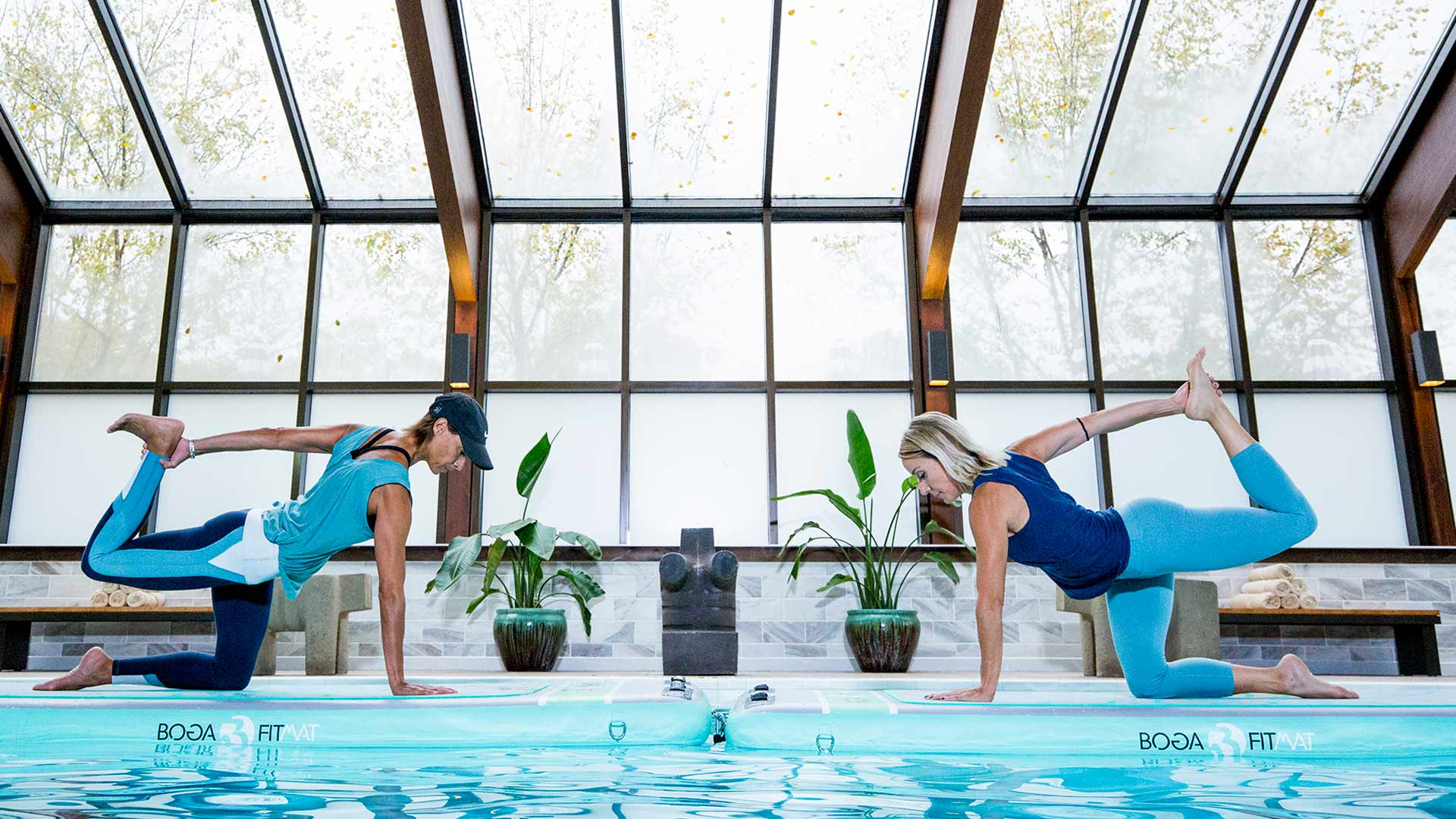 two people in blue workout gear are stretching by the edge of a pool