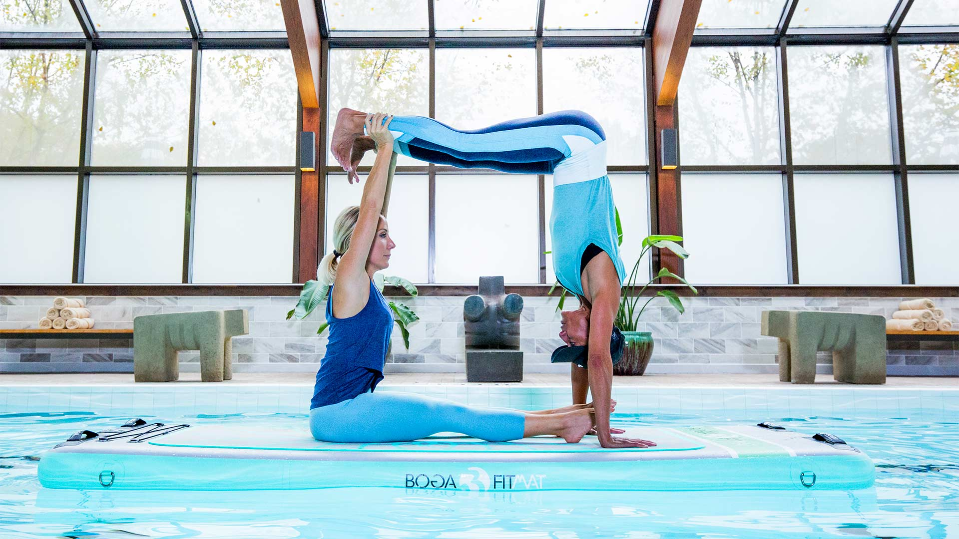 two people doing yoga positions on a floating raft in the pool