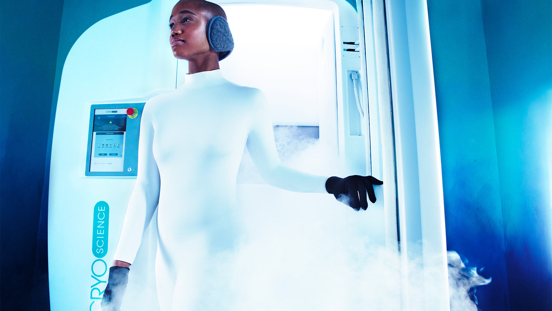 a woman in a futuristic white jumpsuit is walking out of a steam chamber