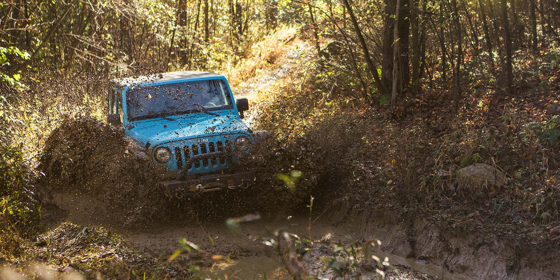 blue jeep driving into mud