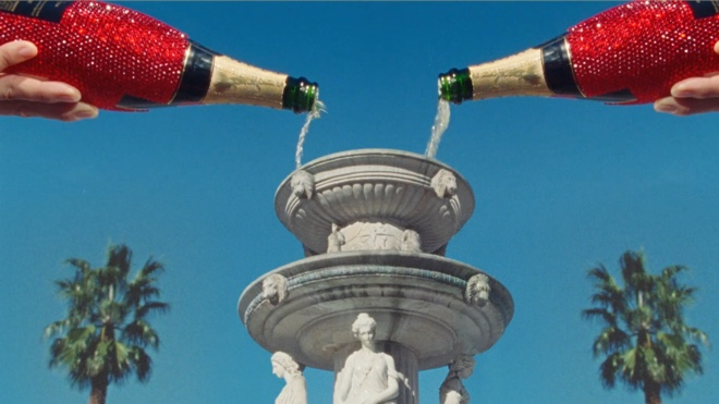 two red jewel bedazzled champagne bottles are being poured into a greek-inspired two-story fountain. There is a blue sky and palm trees in the background