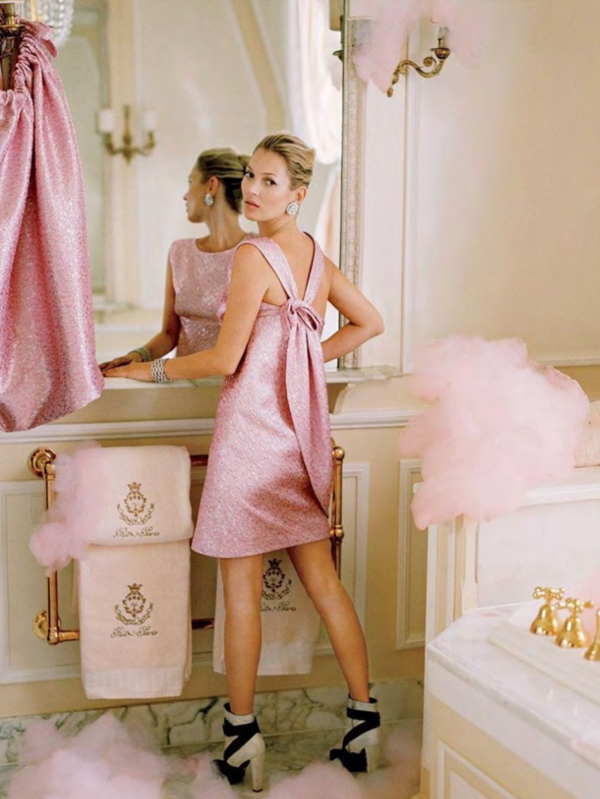 a blond female model in a pink dress with a bow and black and white heeled boots. She is standing in front of a mirror with pink bubble bath bubbles around the room.