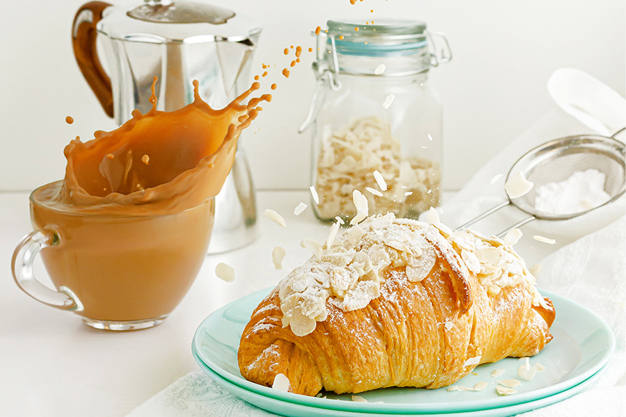 almond croissant with a splashing cup of coffee