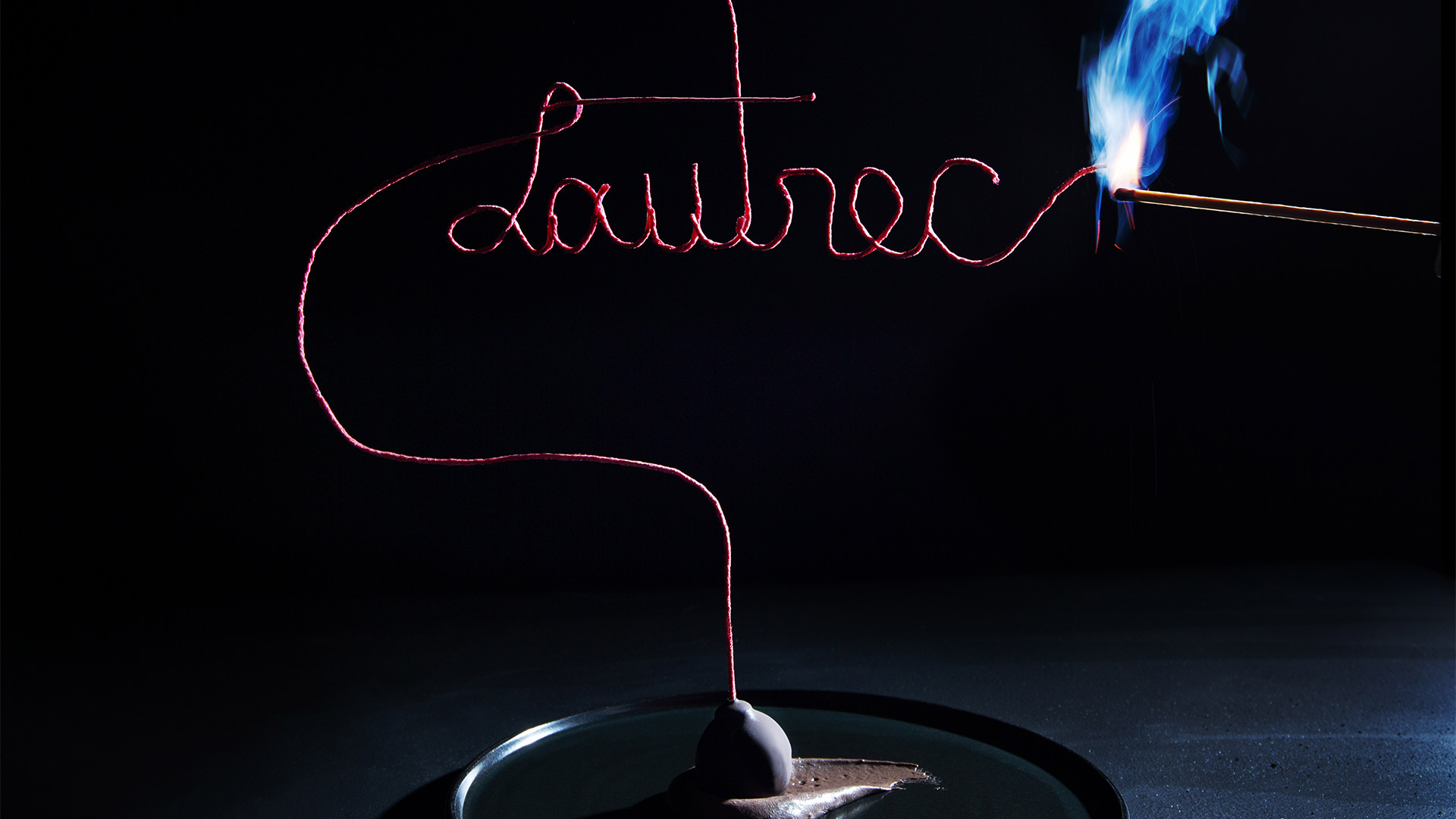 "fancy wick spelling ""Lautrec"" in cursive being lit with a match"