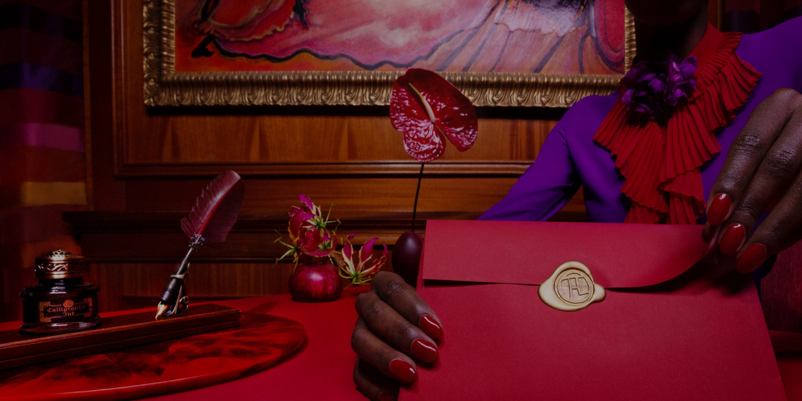 a close up shot of a woman in a purple blouse and bright red nails opening a red envelope.