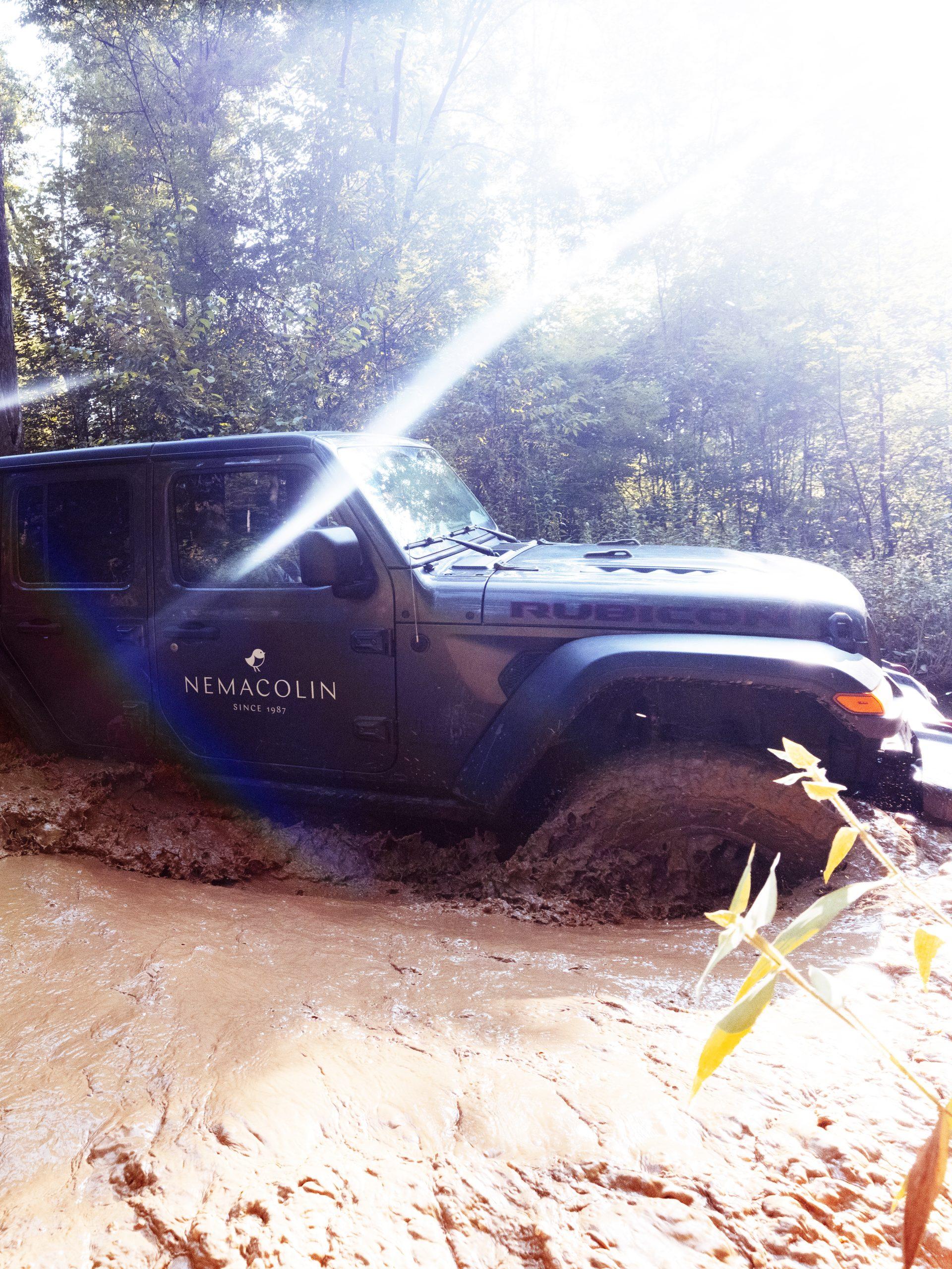 Grey jeep driving through mud