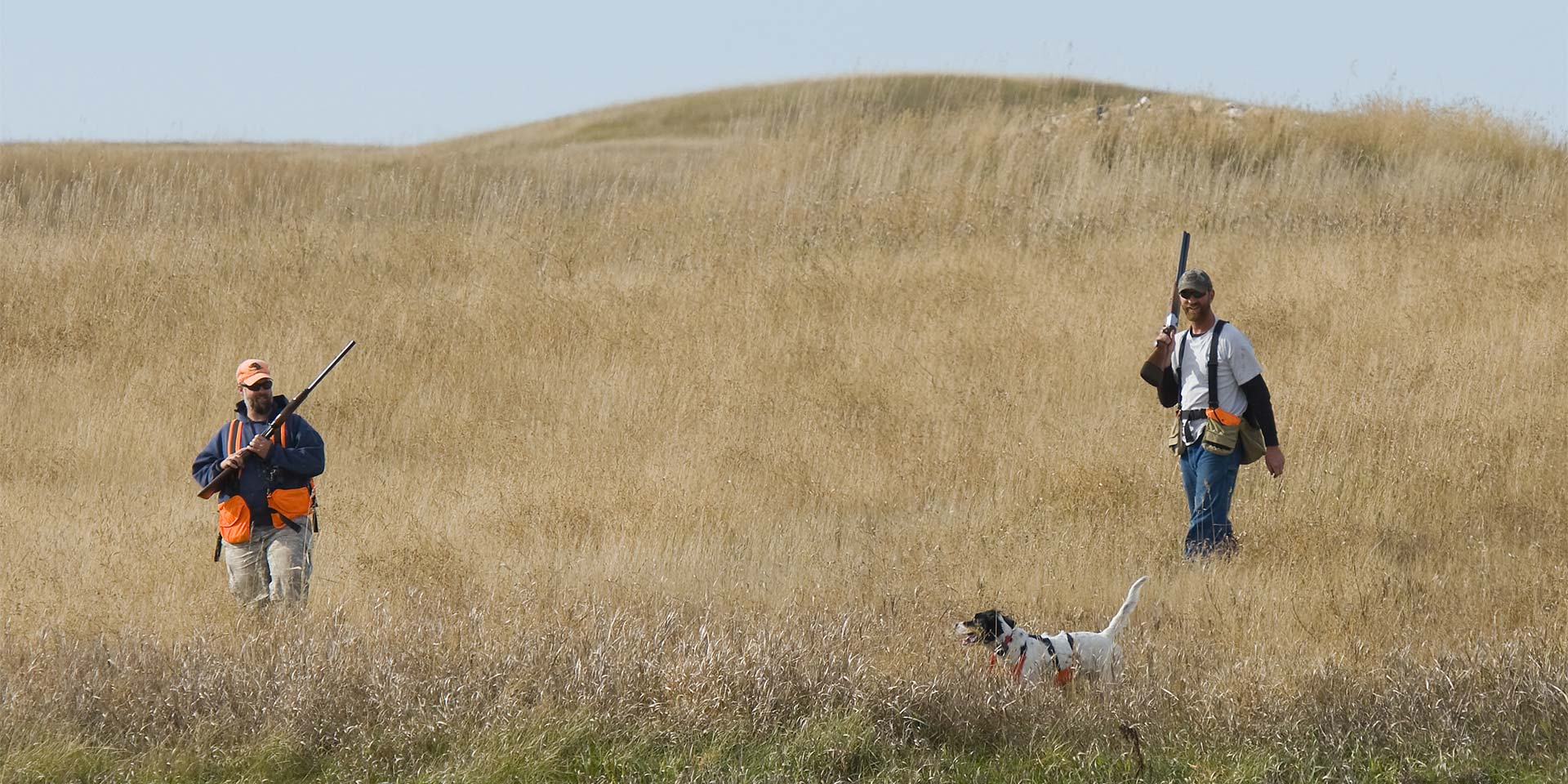 Two men hunting with a dog.