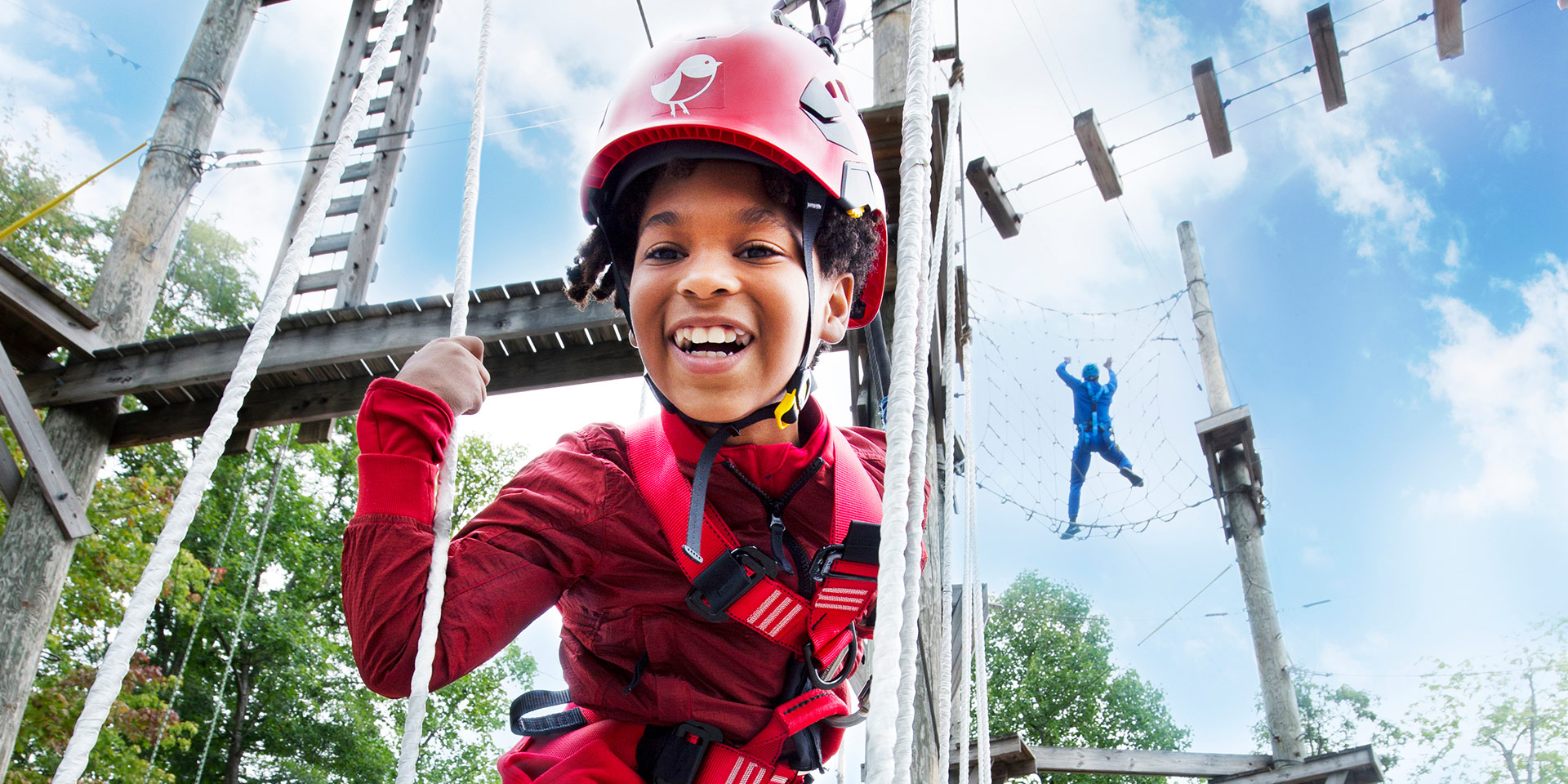 little boy smiling on low ropes course