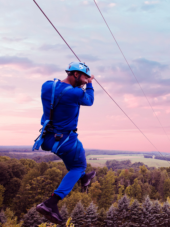 man in blue on zipline
