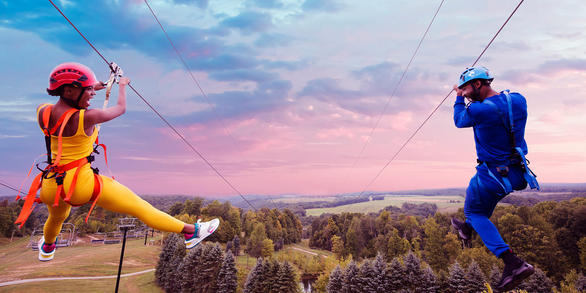 man and woman on a zipline parallel to one another