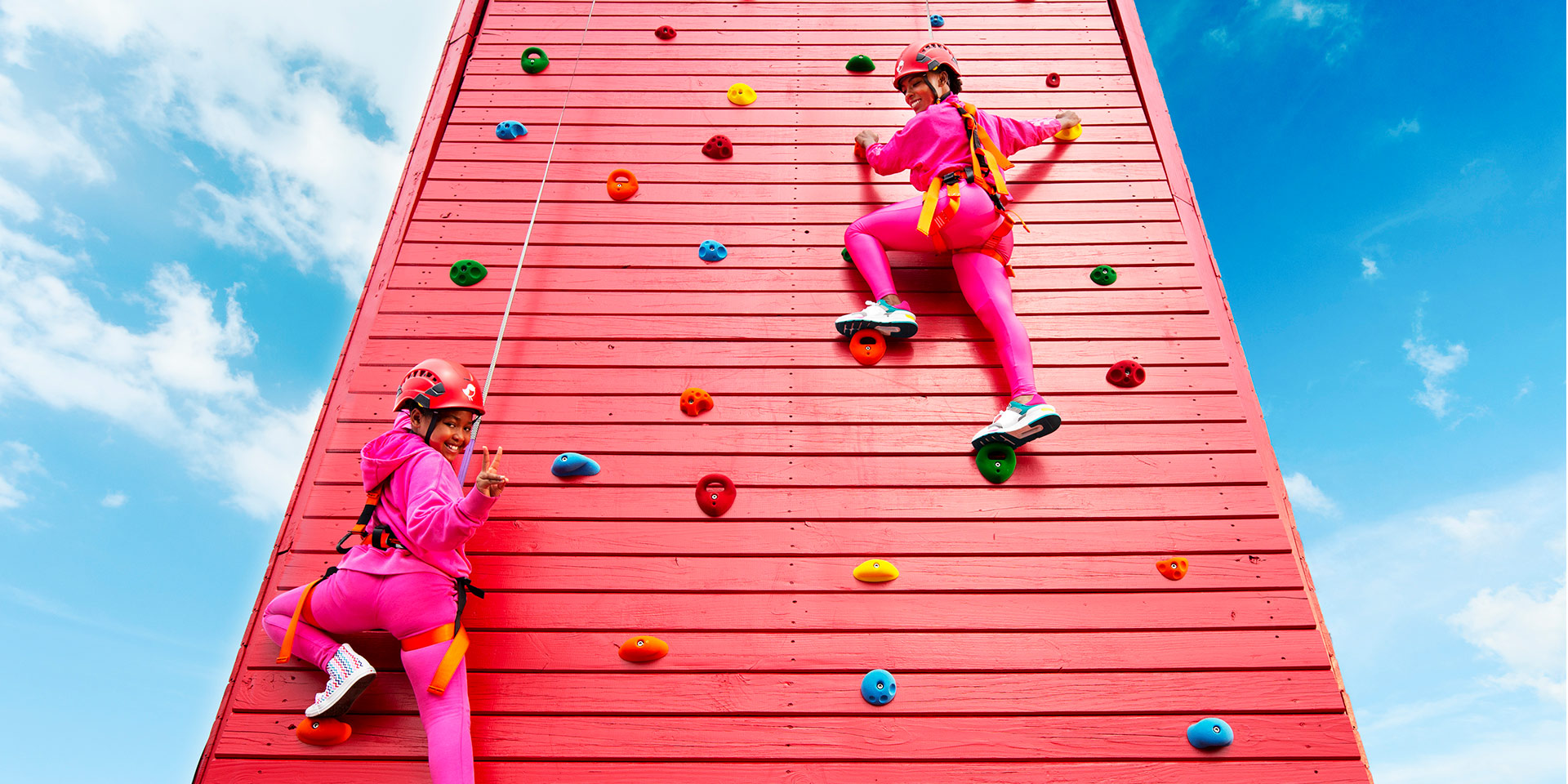two people in pink climbing up a red rock climbing wall
