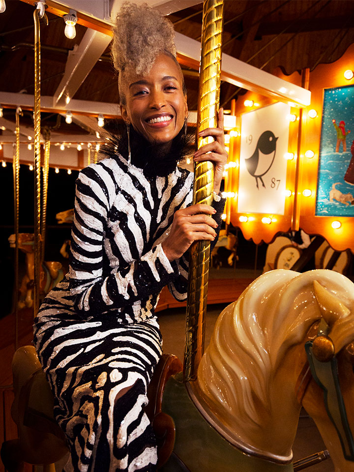 Woman in zebra print dress riding carousel
