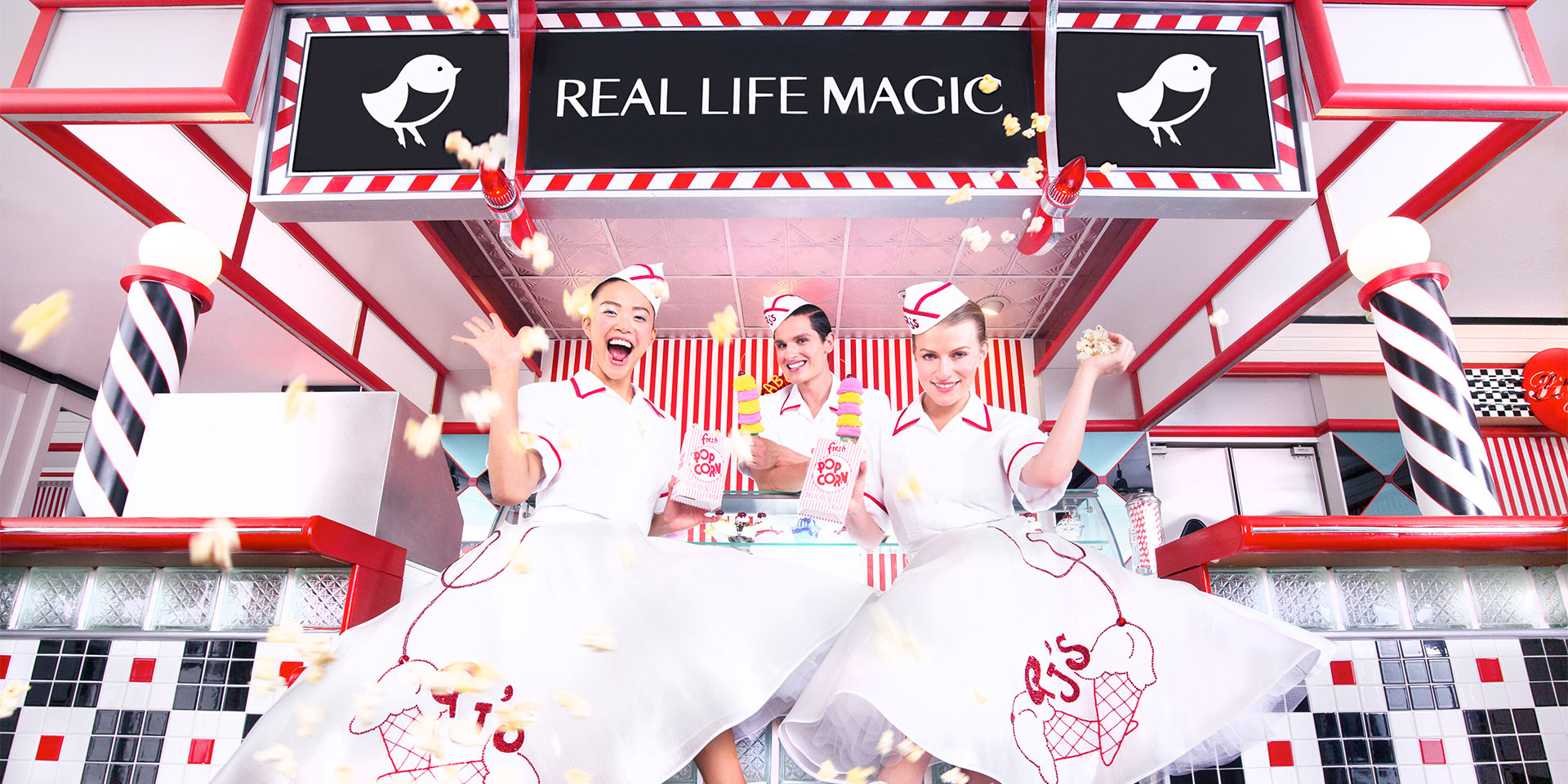 """Real Life Magic"" sign above three girls in big skirts and hats serving ice cream"