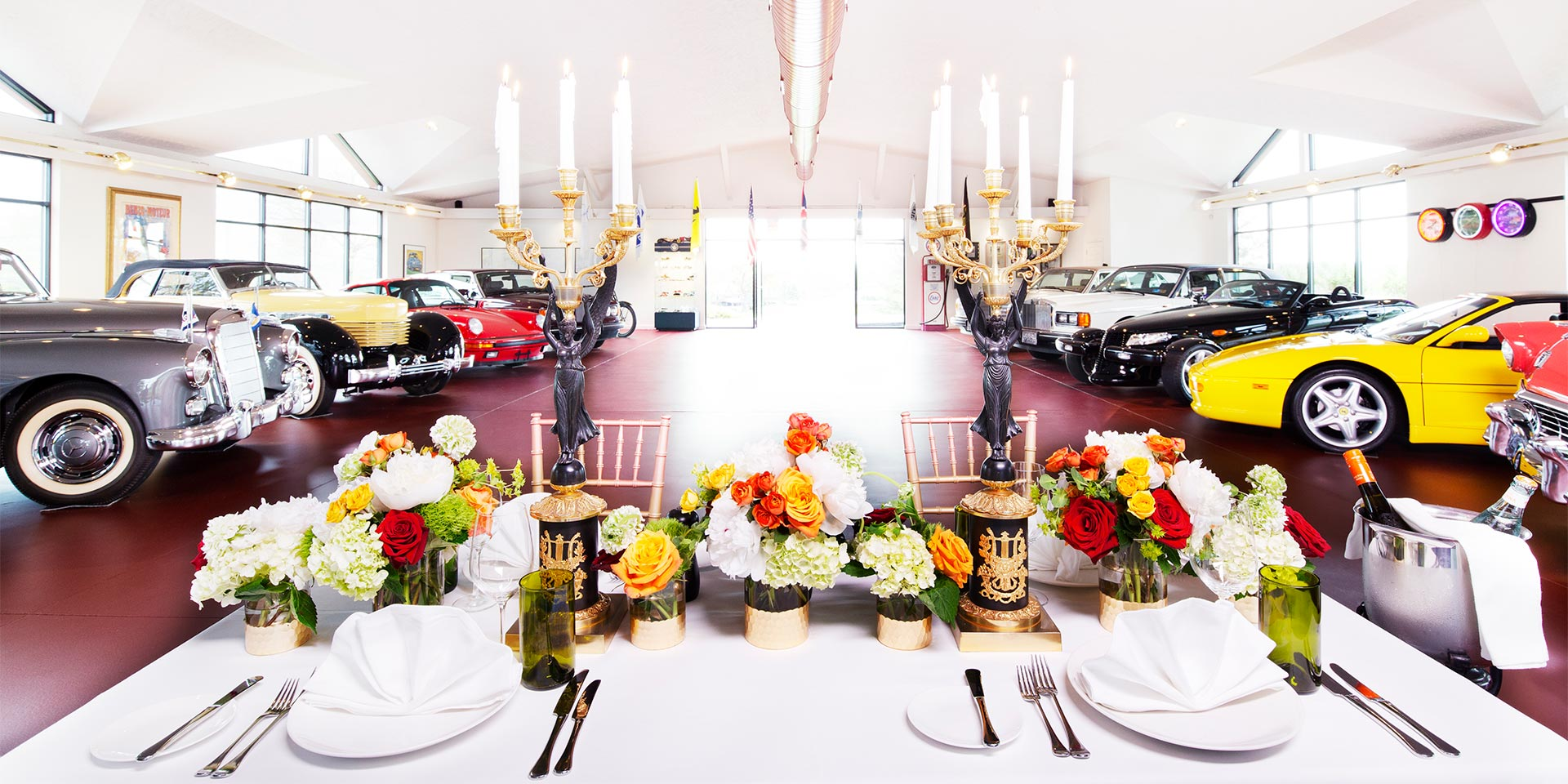 car showroom with table in front with flowers and candles