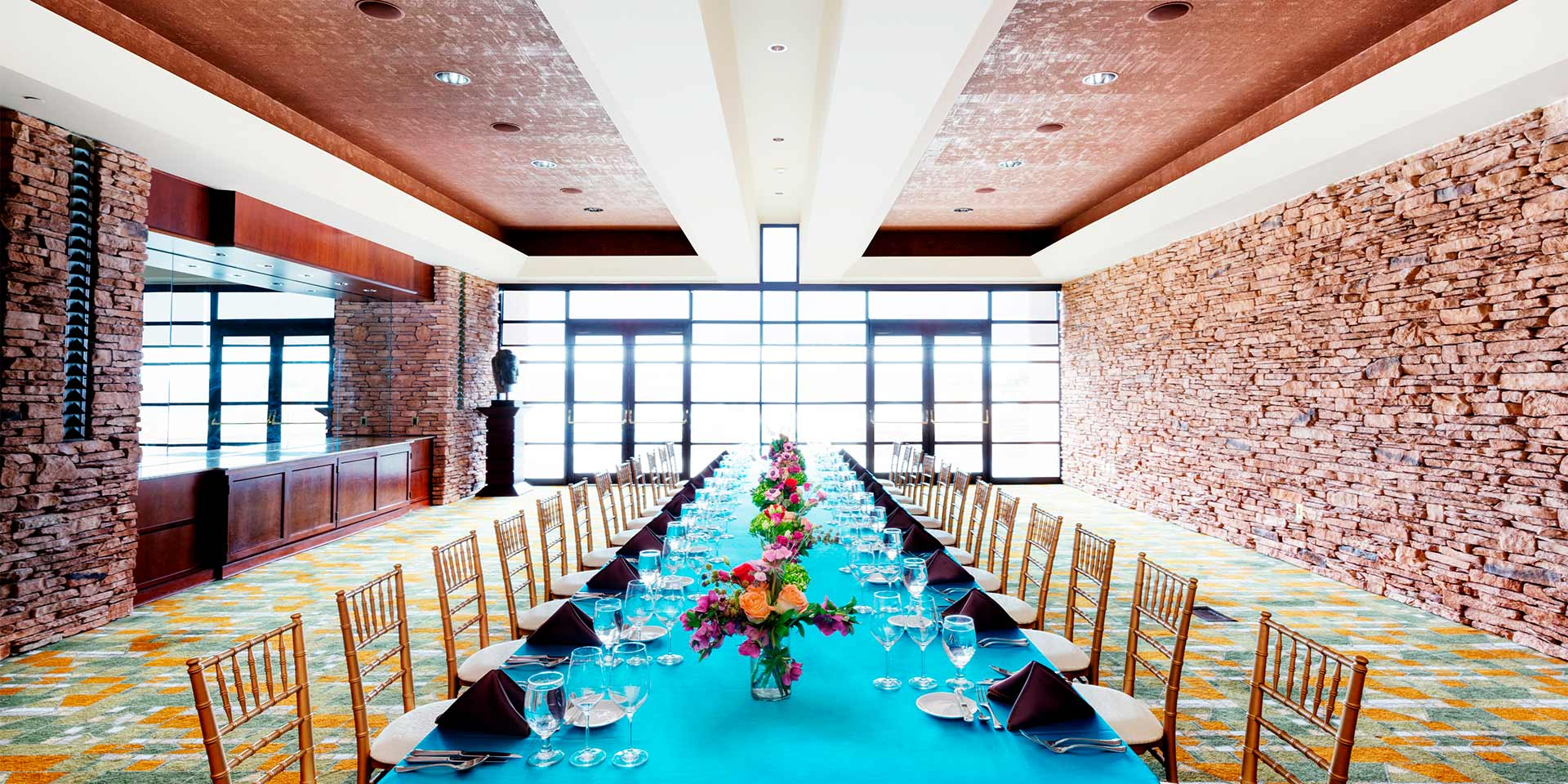 large dining table with blue table cloth and large windows