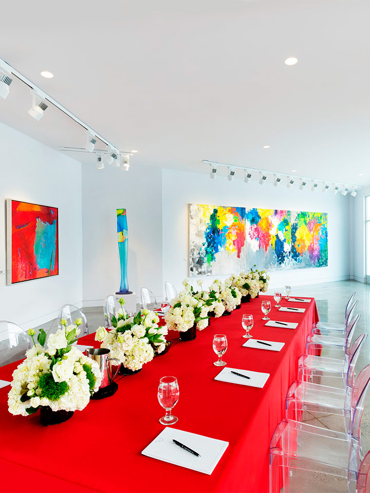 gallery style room with art on the walls and large dining table with red table cloth