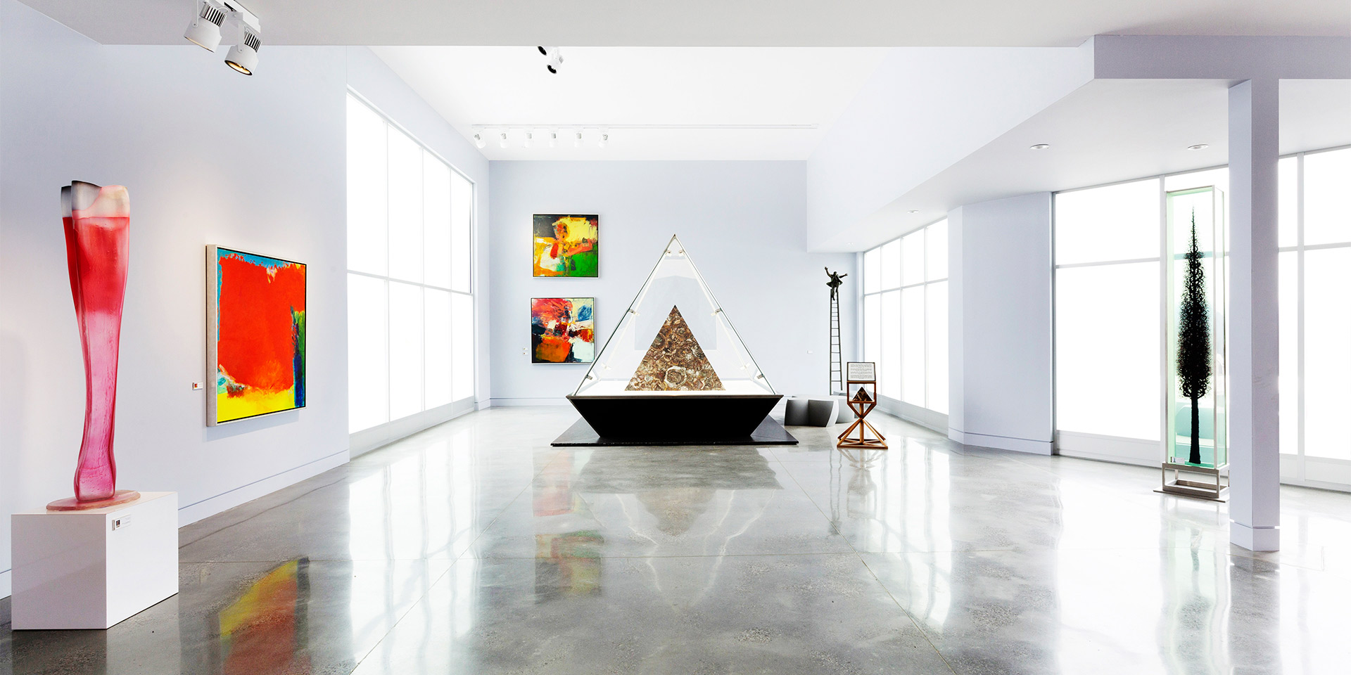 gallery style room with art and large glass pyramid sculpture in the middle