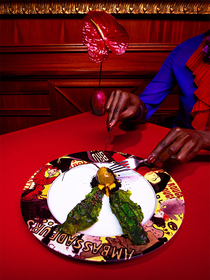 picture of someone cutting food on a patterned plate on a red table