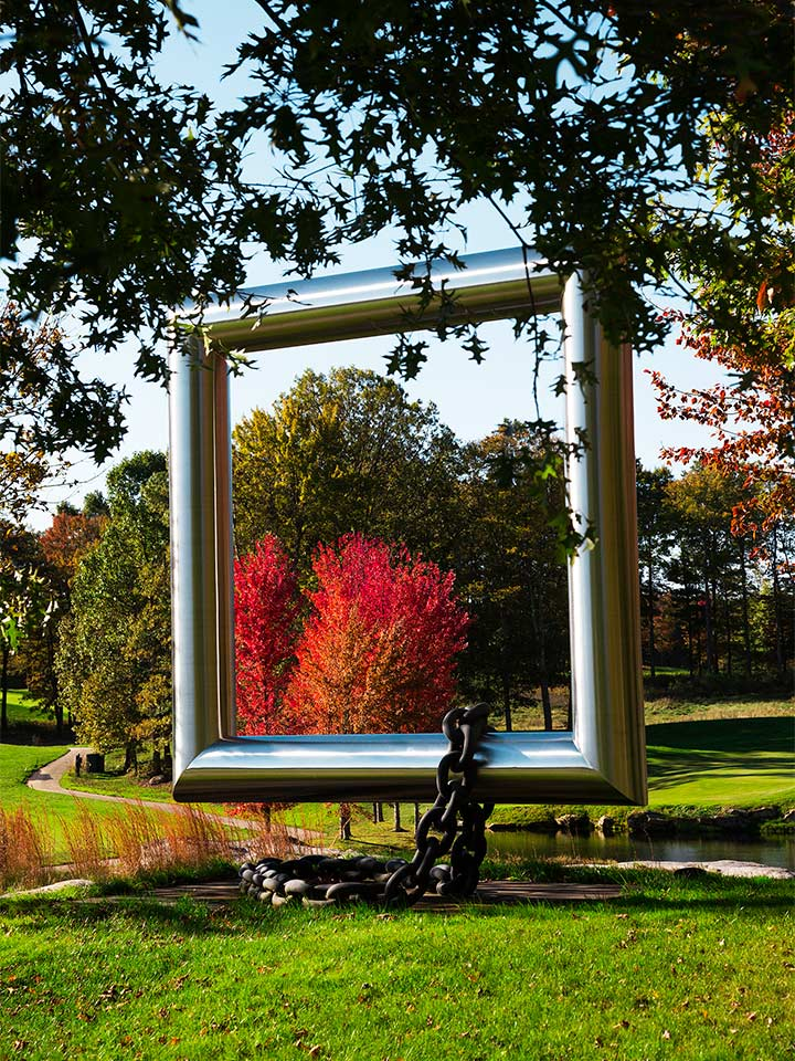 above ground silver 3D square sculpture with chain draped over the bottom outside