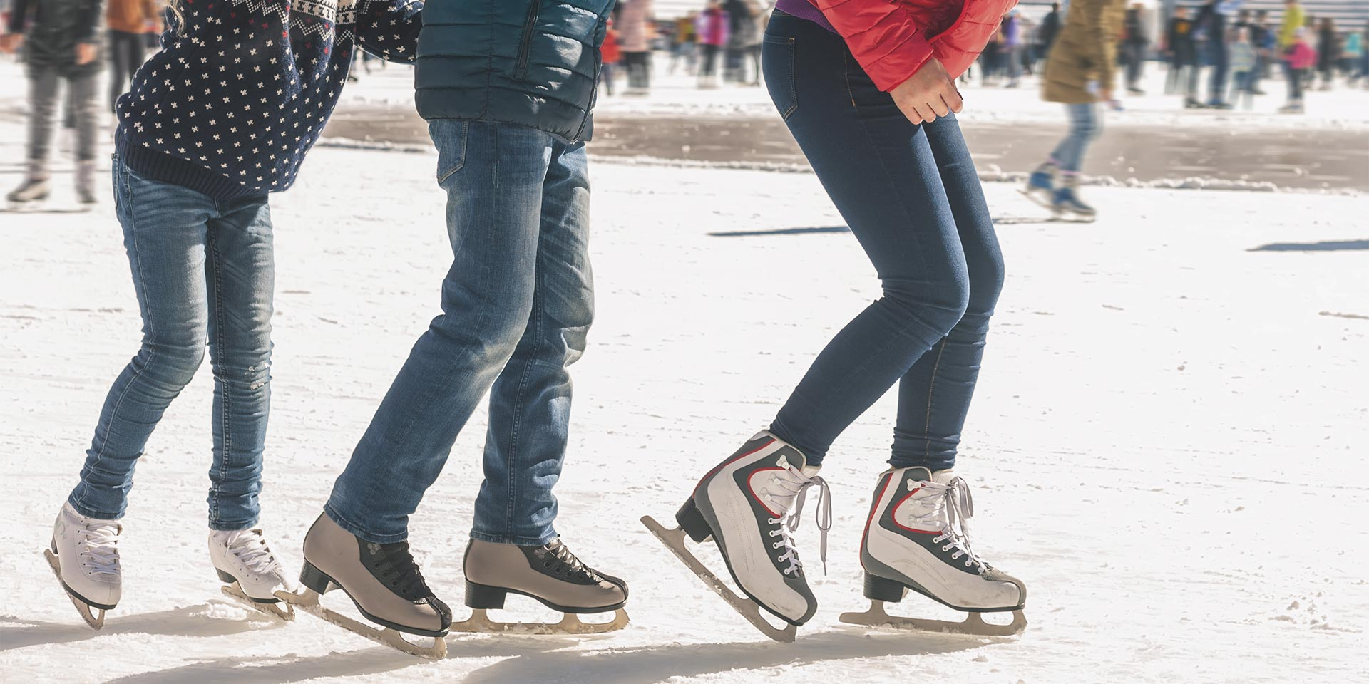 three people ice skating