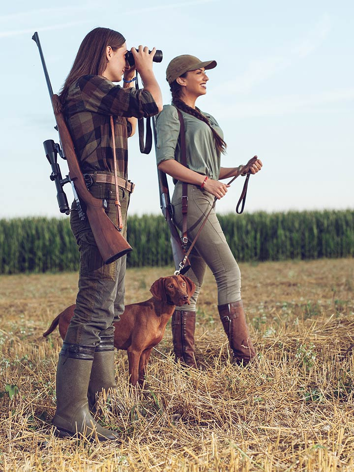 two women and a dog with guns outside