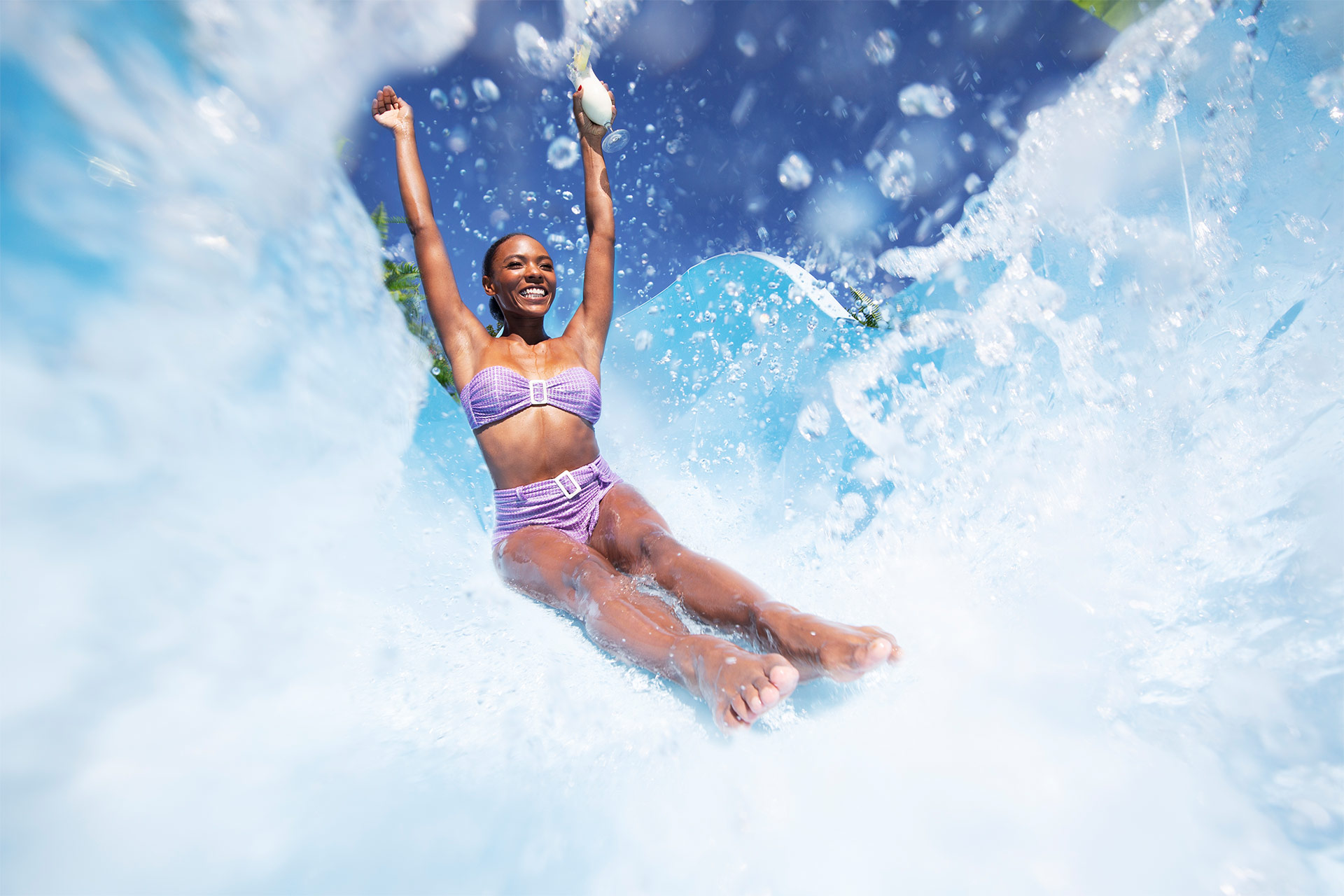 a woman in a purple bikini riding down a waterslide