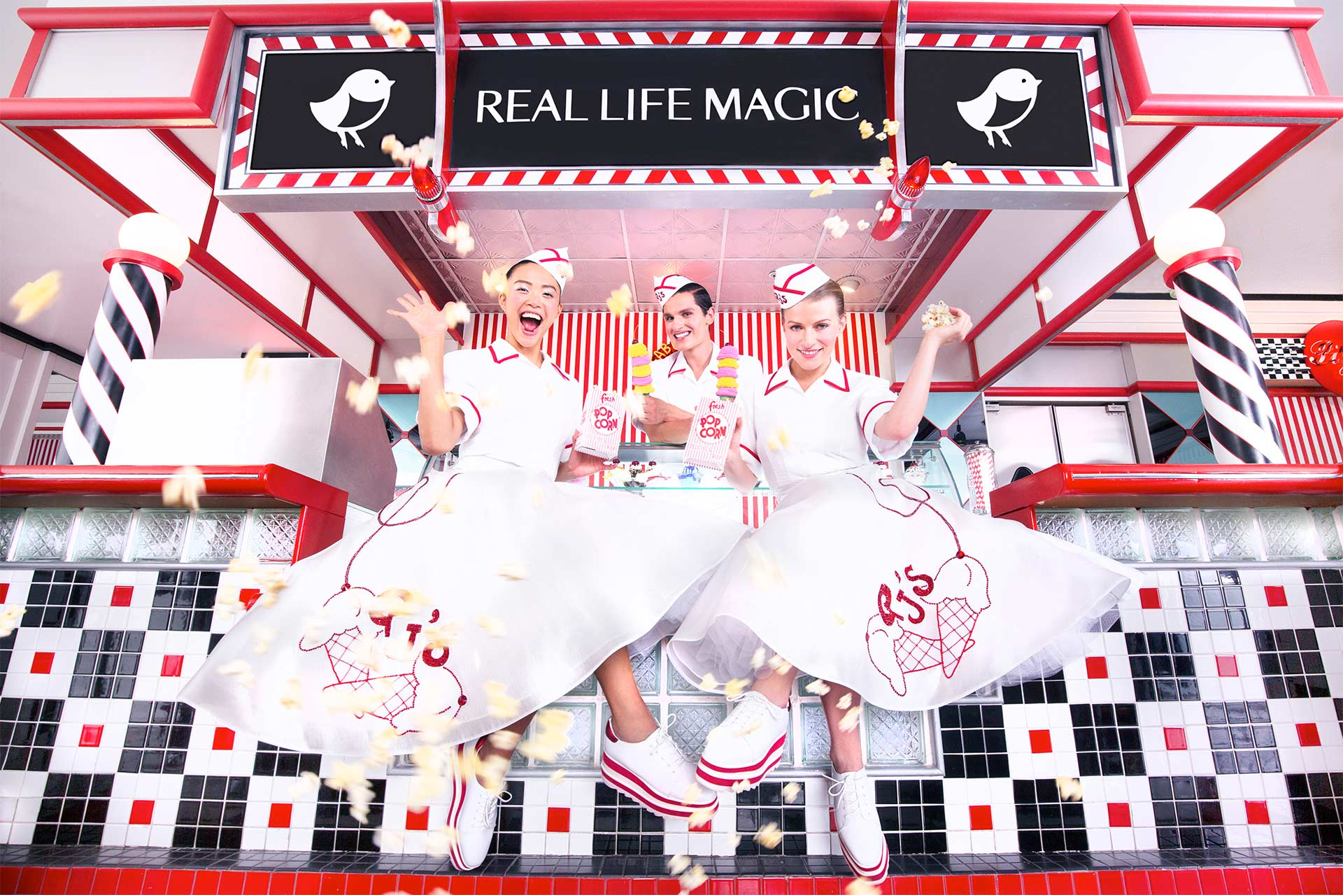 "Three women dressed in 60's style uniforms in front of an ice cream shop with a sign that says ""Real Life Magic"""