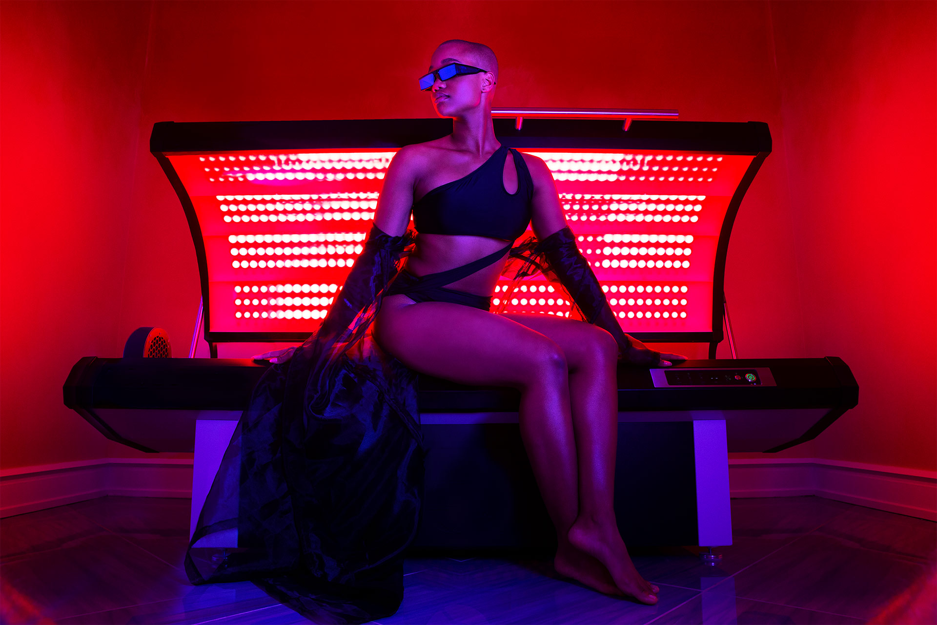 A woman in a red room sitting on top of a tanning bed with red lights within