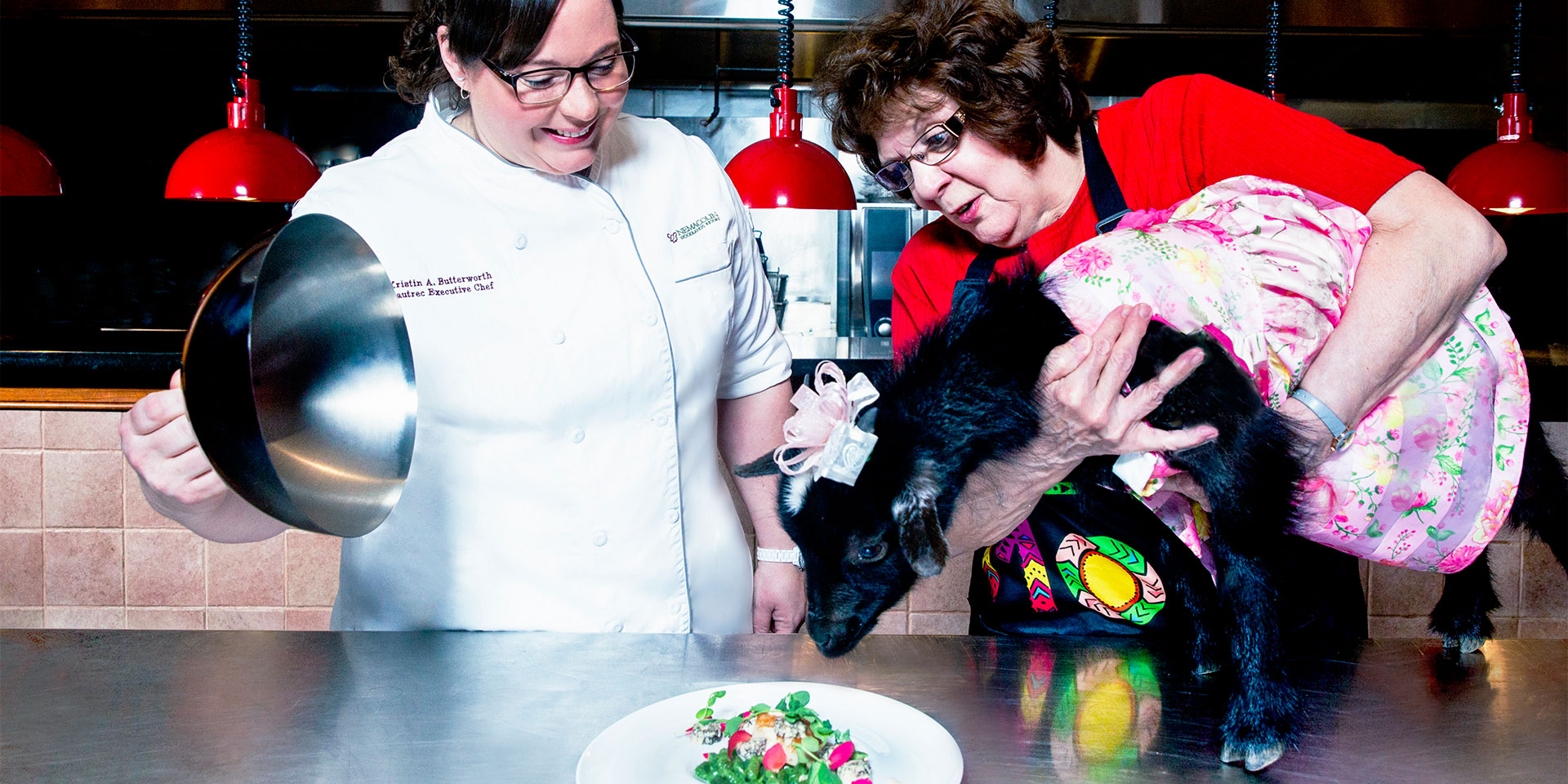 a chef revealing a plate and a woman holding a goat in a dress up to the plate