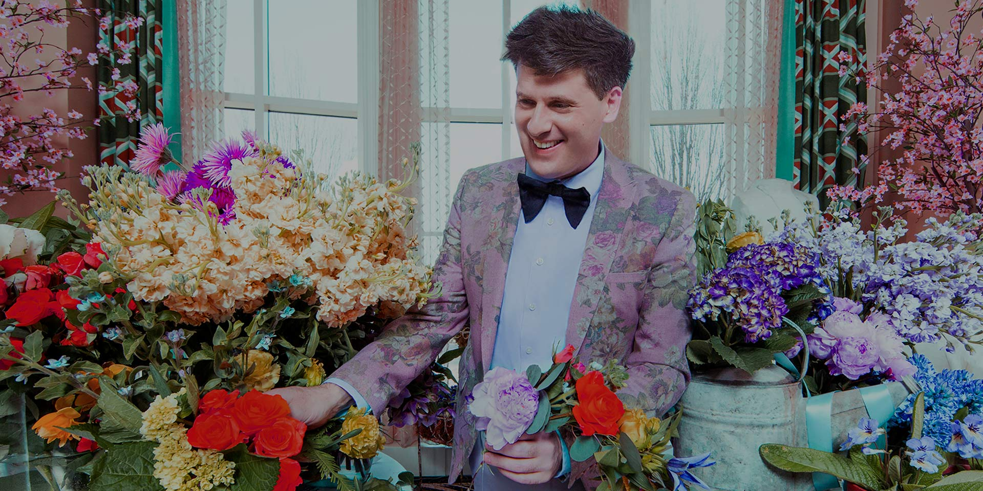 man in pastel suit and bowtie surrounded by flowers