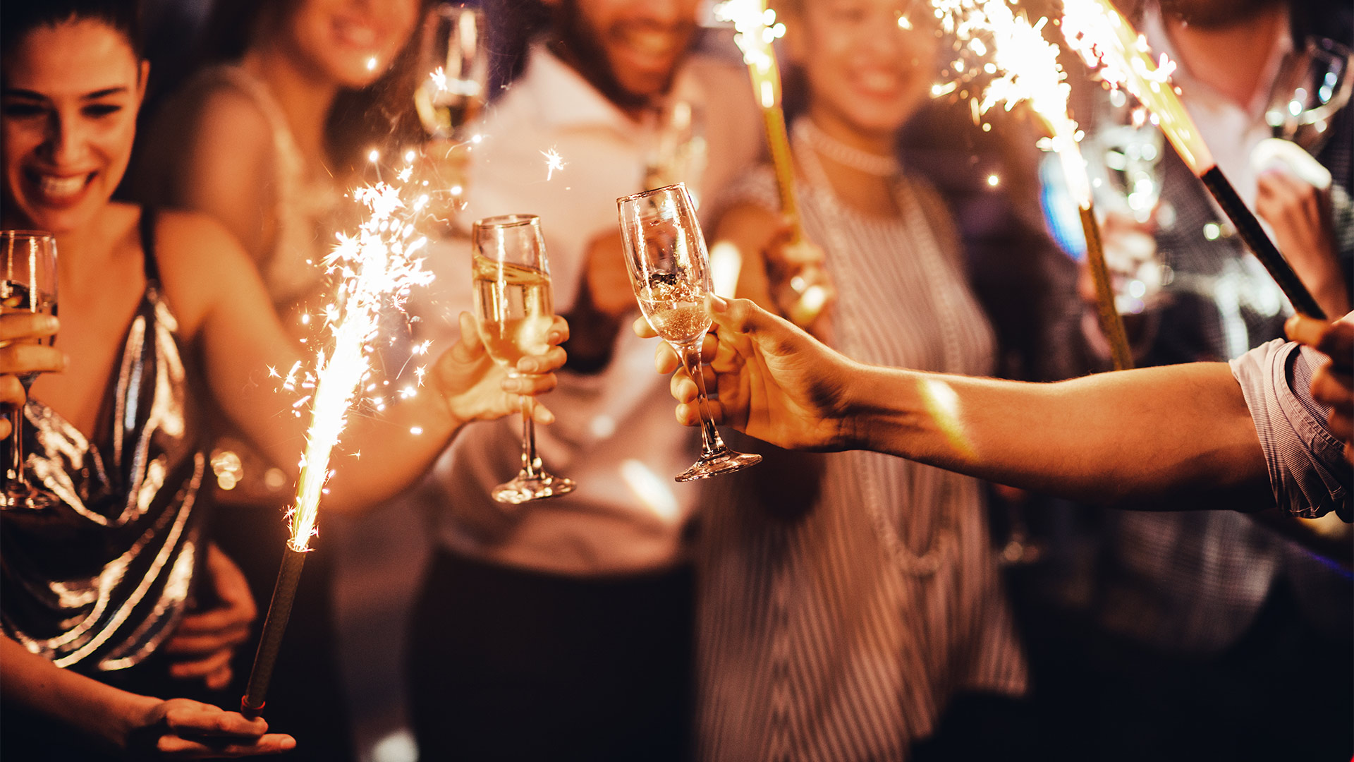 party of people holding champagne and sparklers