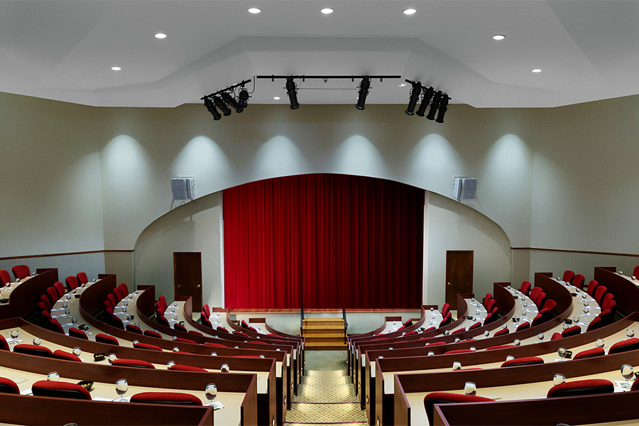large semicircle auditorium with red curtains on stage