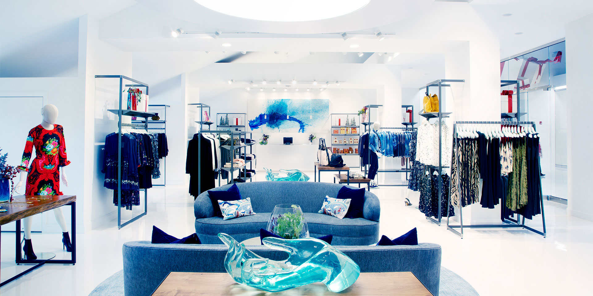 interior of a white fancy clothing store with blue couches