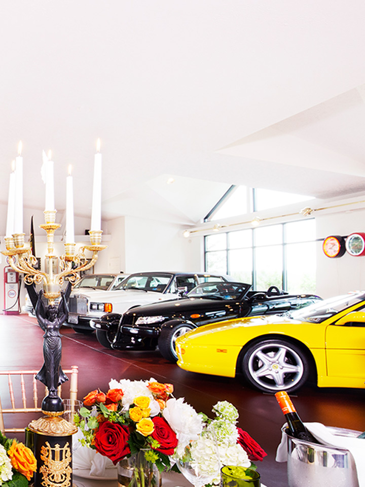 three cars in a showroom with flowers and candles in front