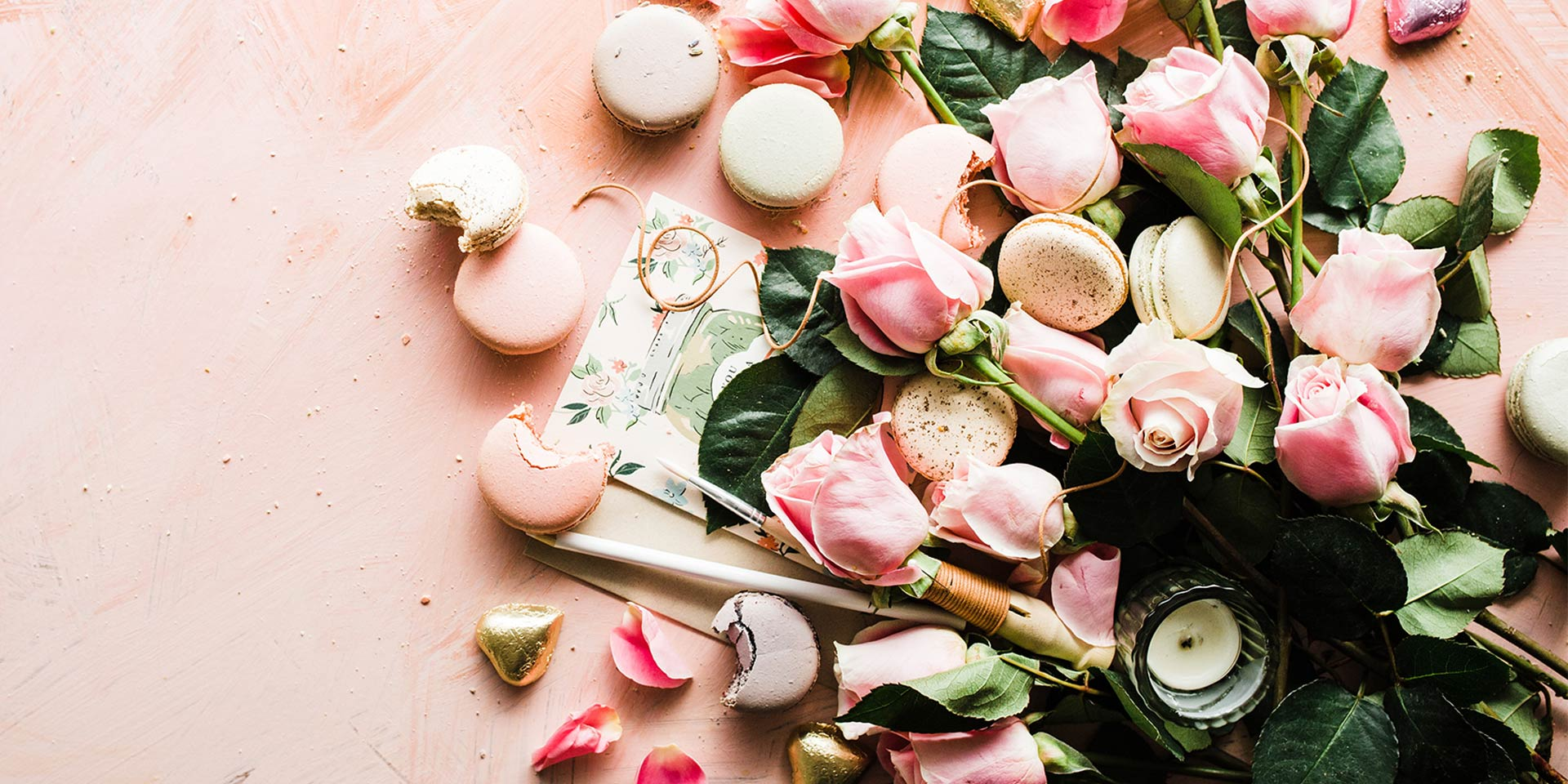 A beautiful array of pink roses with pink and white macarons scatter on a dusty baby pink background.