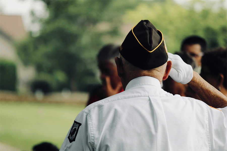 the back of the head of a man in a veteran's cap
