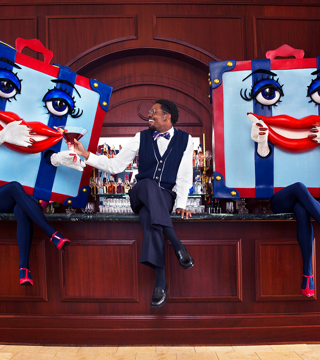 a man sitting on a bar in between two costumed women dressed with boxes as heads
