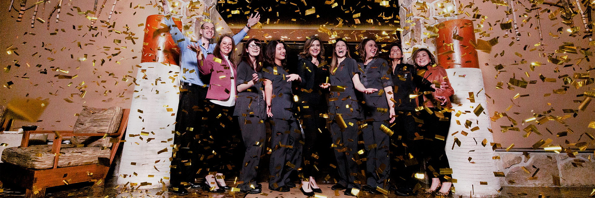 A group of women standing and smiling with confetti in the air