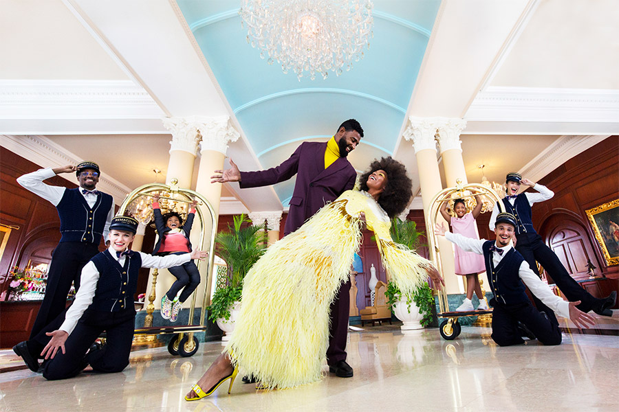Beautiful couple dancing together in the lobby of a hotel with the staff smiling and surrounding them