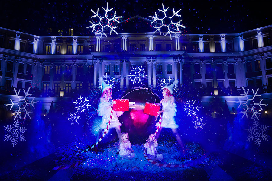 Christmas light setup with glowing snowflakes in front o fa large building and two people dressed as elves in the front putting together a giant electrical outlet