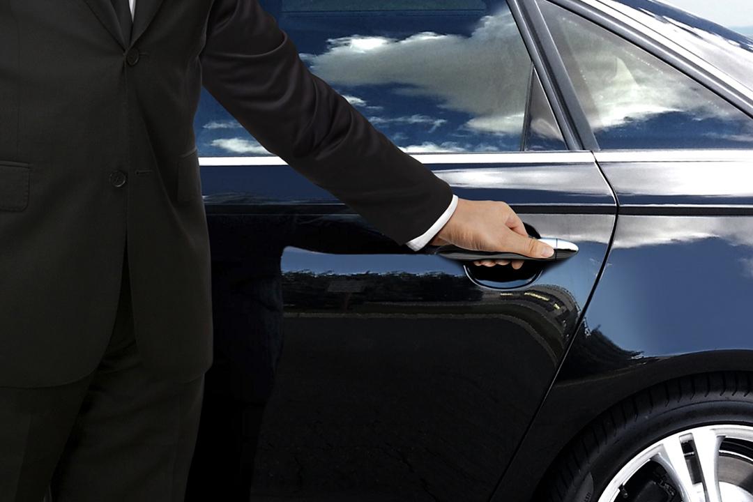 a chauffeur opening the door to a balck sleek car.