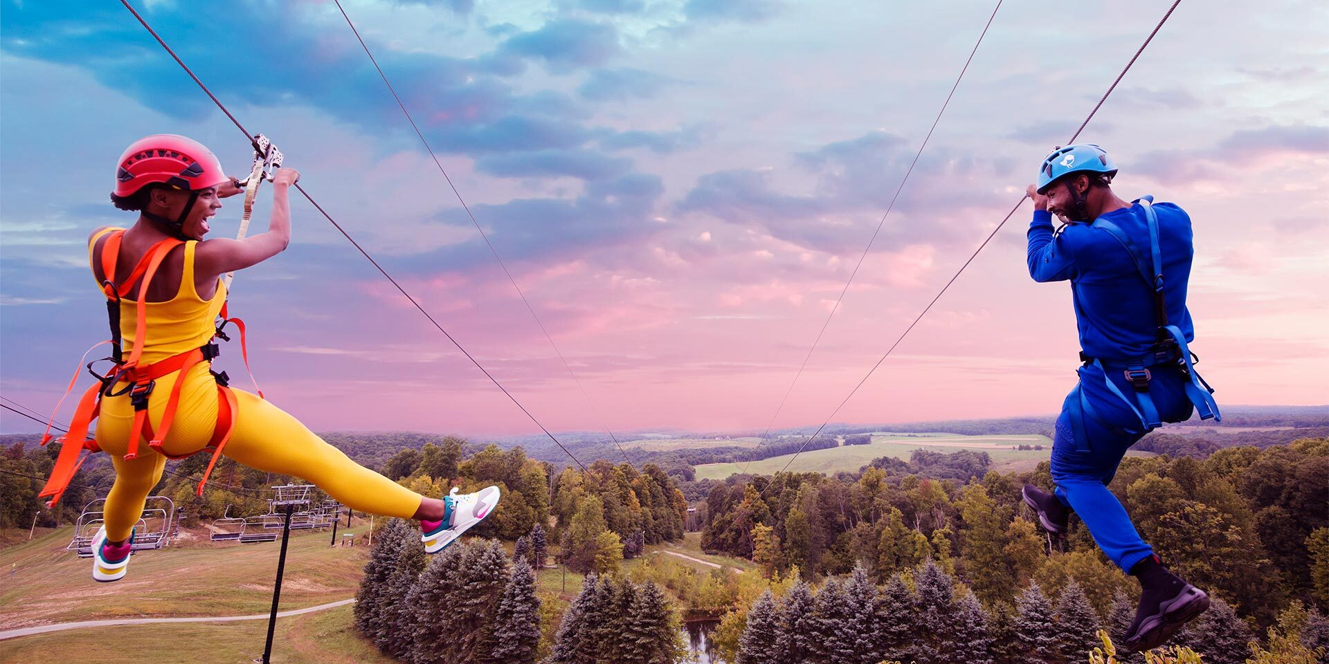man and woman ziplining parallel to each other
