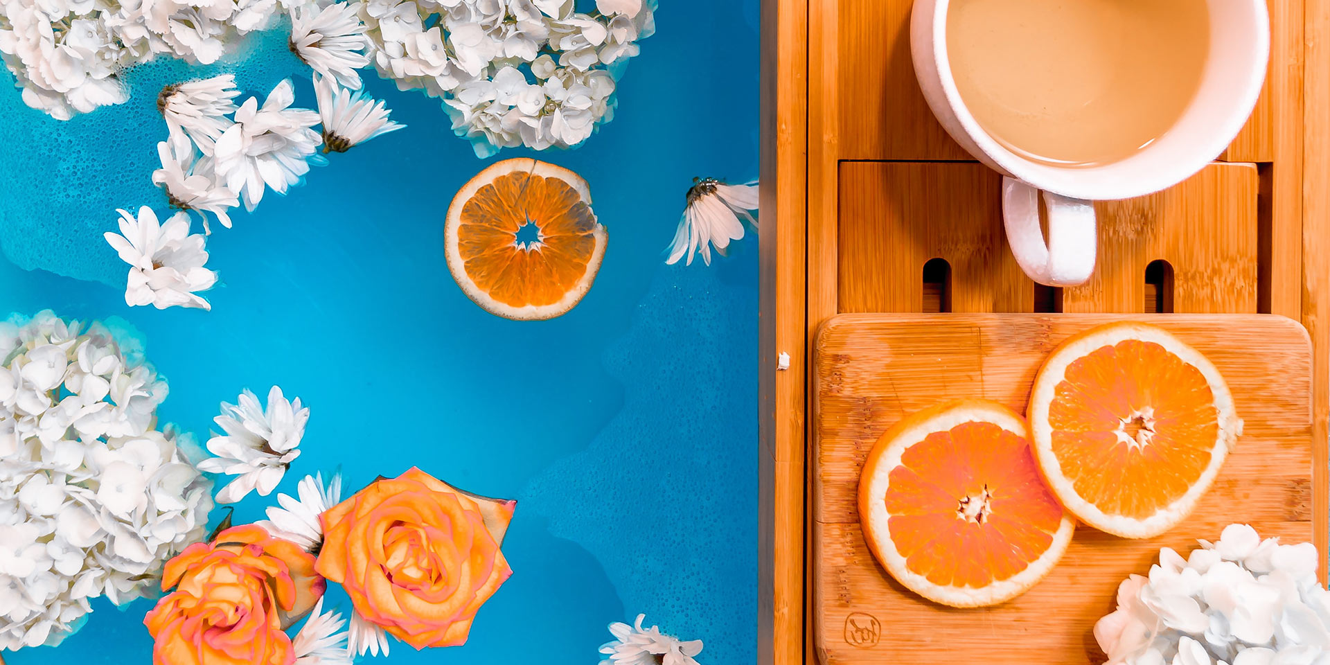 A bubble bath decorated with flowers and oranges with a cup of tea on the side.