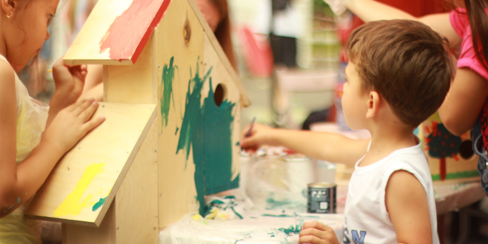 Kids painting a a wooden house.