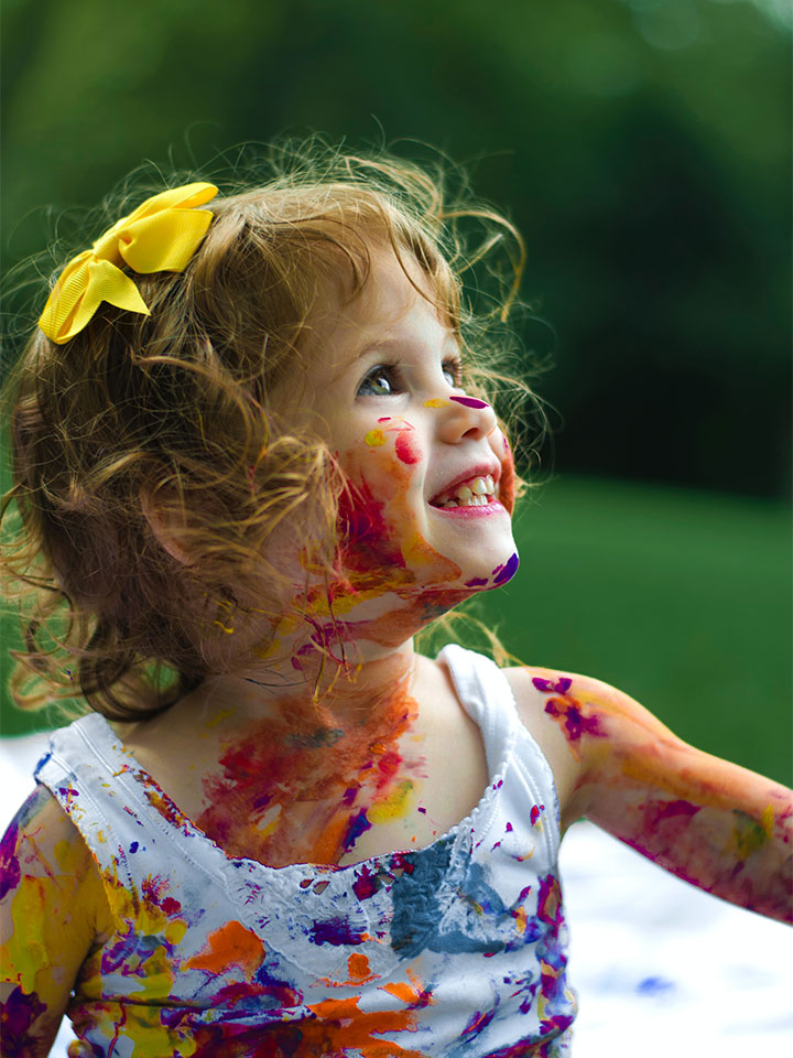 A little girl with paint all over herself smiling.