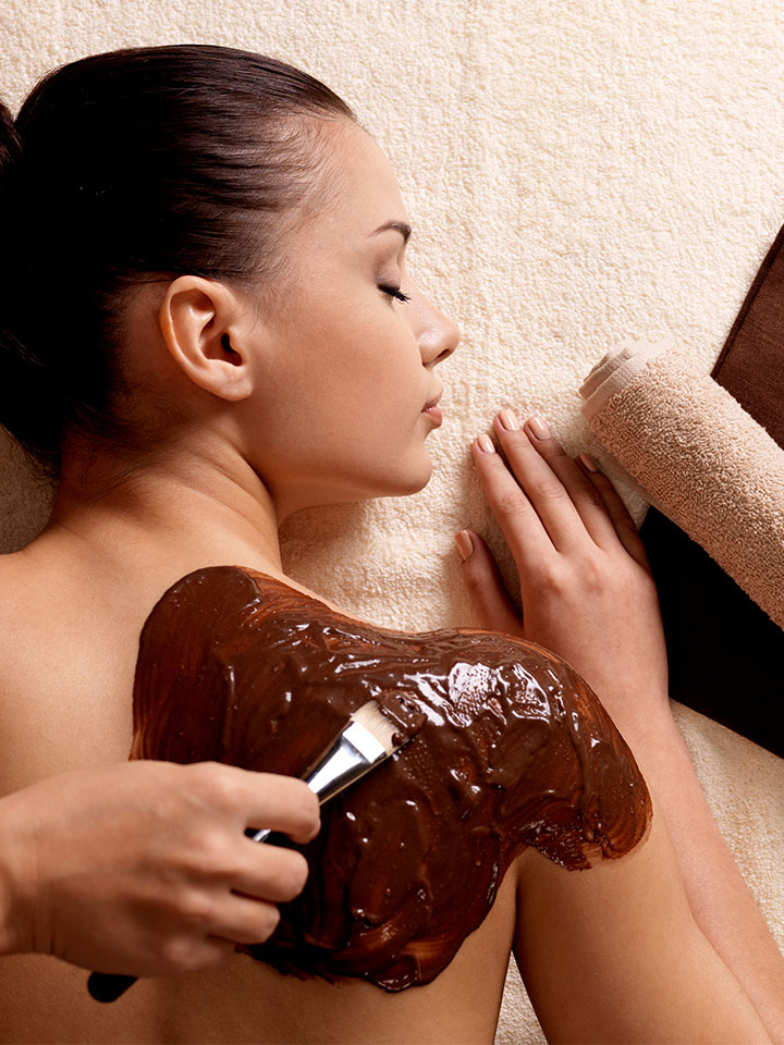 "A woman getting a chocolate ""back facial""."