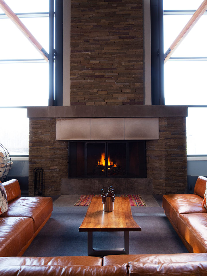 Brown leather seats in front of a fireplace.