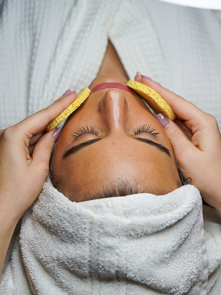 A woman is relaxing while getting a soothing facial.
